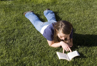 [teenager reading, on a grassy lawn]