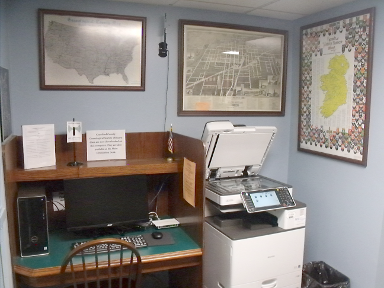 [photo: computer, photocopier, and framed maps]